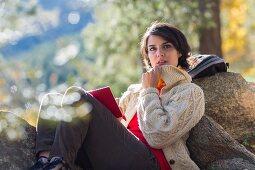 Frau in Wanderkleidung sitzt mit Buch verträumt an Felsen gelehnt auf herbstlicher Waldlichtung