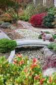Stone bridge spanning gravel bed in Japanese-style garden