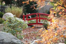 Red-painted wooden bridge spanning gravel bed in Japanese-style garden