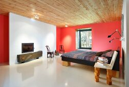 White chimney breast in red bedroom with bed and chair on wooden-block legs