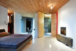 Purist bedroom in modern building: rustic stone slab under glass-fronted fireplace