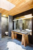 Designer bathroom with washstand on rustic wooden trestles, grey tiles and skylight shaft in wooden ceiling