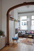 Blick durch breiten Durchgang mit geschnitztem Holzrahmen in Jugendstil und Blick auf Kind, auf gemütlichem Sofa vor Fenster