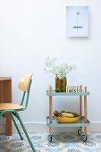 Servierwagen in Fiftiesstil mit Blumenvase und Obstschale vor Wand, daneben schlichter Holzstuhl, auf gemustertem Fliesenboden