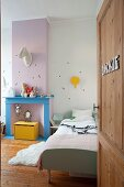 Blick durch offene Tür ins Kinderzimmer, Bett neben farbig gestaltetem, ehemaligem Kamin, oberhalb Deko Tierkopf an Wand