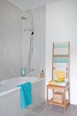 Holzhocker mit leiterartiger Lehne für Handtücher, neben Badewanne im Badezimmer