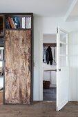 Selbstgebautes Regalelement mit rustikaler Bretterfront, Blick durch offene Tür auf Garderobenhaken in der Diele