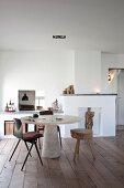 Puristischer Raum mit Dielenboden und gemauerten Nischen, runder Tisch mit konischem Betonfuss und Baumscheiben-Hocker
