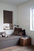 Plüschelefant auf puristischem Kastenbett, darüber eine Wandnische mit Spiegel und Holzkiste als Nachttisch