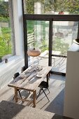 Blick von oben auf rustikalen Holztisch, einfache Schalenstühle und Retroleuchte in lichtdurchflutetem Raum mit Ceppo-di-Gre Steinboden