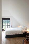 Doppelbett mit weisser Bettwäsche in Schlafzimmer mit Dachschräge und Sprossenfenstertür