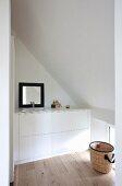Minimalistischer Einbauwaschtisch mit schwarz gerahmtem Spiegel unter Dachschräge