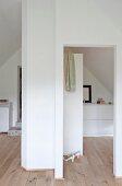 Weisse Einbauten und heller Dielenboden in Schlafraum unterm Dach mit Bad Ensuite