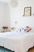 Double bed with white lace bedspread and patterned scatter cushions below white shelf on wall