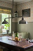 Retro pendant lamp with chrome lampshades above solid-wood table in corner of dining room