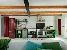 Open-plan kitchen in rustic interior; counter with green-painted base units, dark red fridge-freezer