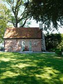Small, traditional brick house with external chimney in sunny garden