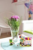 Posy of carnations in glass vase and toys