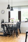 Black Thonet chairs around dining table below pendant lamps with black lampshades next to window