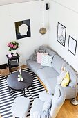 View down onto grey sofa set, round coffee table and black and white striped rug in corner of living room