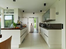 Gegenüberliegende Küchenzeilen in offener Küche mit grossformatigem Fliesenboden, im Hintergrund Durchgang mit Blick in Eingangsbereich
