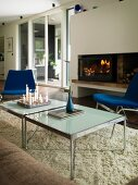 Lit candles on modern coffee table on pale flokati rug in front of fire in open fireplace