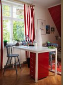 White desk, red filing cabinet and red and white striped curtains in child's bedroom