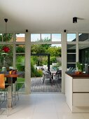 Open-plan kitchen with dining area next to glass wall, open terrace doors and view of outdoor seating area
