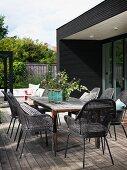 Graue Geflechtstühle um rustikalem Holztisch auf Terrasse mit Holzdeck