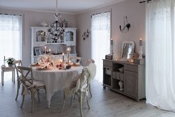 Lit candles on festively set table in vintage-style dining room