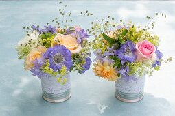 Two posies of roses and scabious in decorative tins
