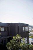 Antrazithfarbene Metallfassade eines modernen, kubischen Wonhauses mit Blick über Brisbane