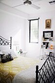 Yellow floral bedspread on black metal bed in front of small ladder-style shelves of ornaments