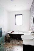 Modernes, schwarz-weisses Bad mit Travertinboden, orientalisches Ablagetischchen und Wannentablett aus Holz