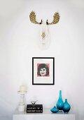 Stilisiertes, goldbemaltes Hirschgeweih und kleines Popart-Bild über skandinavischem Kerzenständer und eleganten, blauen Glasvasen