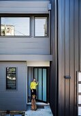 Dog and woman in front of grey metal façade of modern, cubist house in Brisbane, Australia