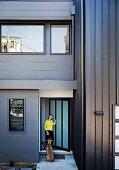 Hund und Frau vor der antrazithfarbenen Metallfassade ihres modernen, kubischen Wonhauses in Brisbane