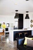 Markante Pendelleuchten über Küchentheke mit Retro Hockern, Frau und Hund in der offenen Einbauküche im Hintergrund, vorne Ledersessel mit Dekokissen