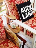 Black and white scatter cushion printed with 'Auckland' motto on floral armchair next to magazine rack