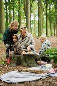 Family having autumn picnic in woods