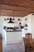 Schlichte Einbauküche mit freistehendem Block auf gemustertem Fliesenboden, im Hintergrund Frau
