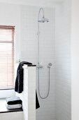 Dusche mit Kopfbrause, seitlich schwarzes Handtuch auf Trennwand in Brüstungshöhe