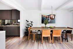 Brown leather chairs around rustic dining table in open-plan kitchen