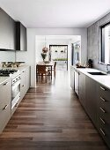 View from designer kitchen into dining area with continuous exotic-wood parquet floor