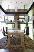 Futuristische Innenarchitektur mit Homeoffice-Bereich in Luxuswohnung, im Vordergrund rustikaler Holztisch mit Eames-Bürostühlen