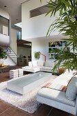 Blick von moderner Designer-Wohnlandschaft mit Zimmerpflanze auf futuristischen Einbau mit Treppe und Innenfenster