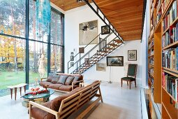 Sofas with wooden frames and leather cushions and side table next to double-height glass wall opposite bookcase below gallery with delicate steel and wood staircase