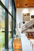 Living room with double-height glass wall and sculpture on glazed strip of floor