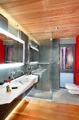Modern bathroom with washstand, back-lit mirror, walk-in shower and toilet