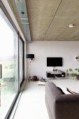 Zeitgenössisches Wohnzimmer mit Fensterfront und Sichtbetondecke, im Hintergrund Stehleuchte mit schwarzem Schirm neben Flachbildschirm an Wand